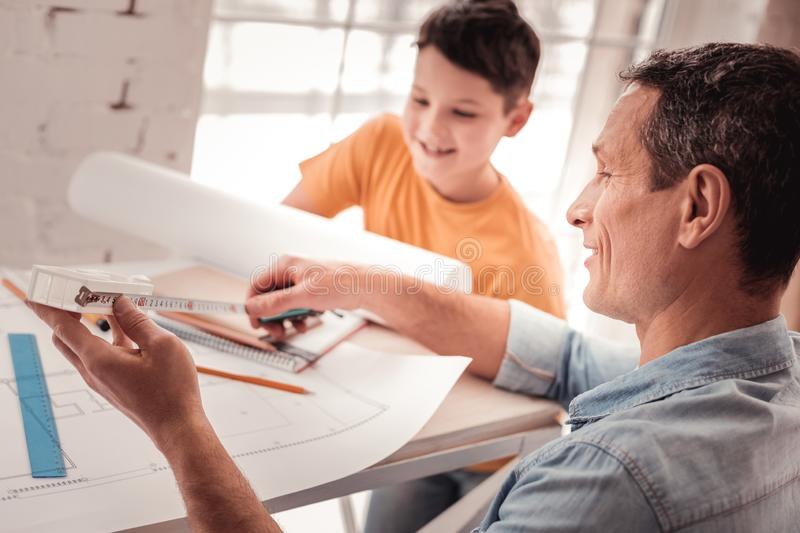 Dark-haired foster father teaching his son geometry royalty free stock photography