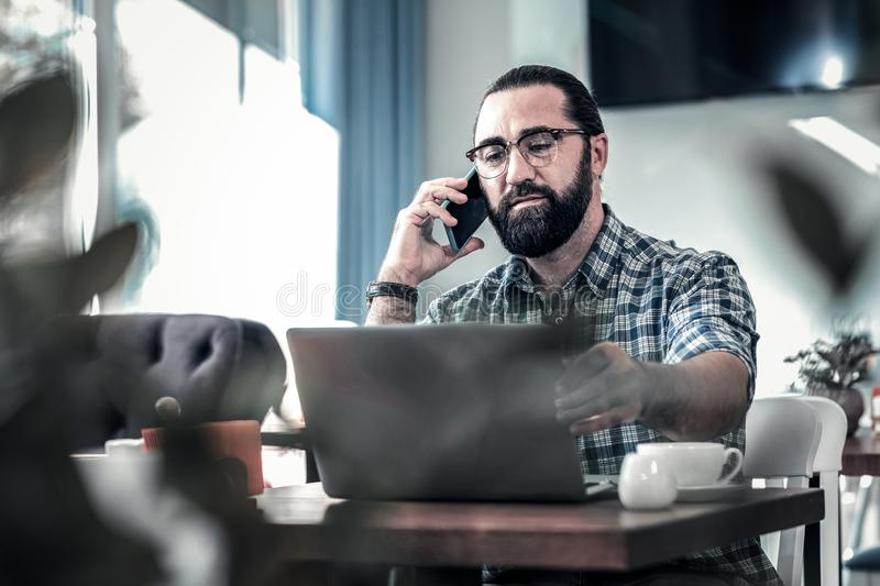 Dark-haired freelance writer calling his colleague working remotely. Call colleague. Dark-haired freelance writer calling his colleague working remotely using royalty free stock images