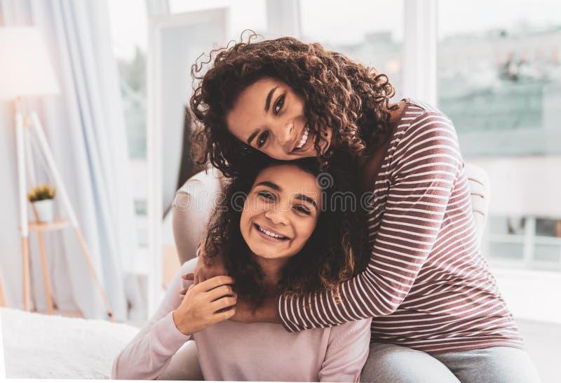 Dark-haired girl feeling loved while hugging her caring sister. Caring sister. Dark-haired beautiful girl feeling very loved while hugging her caring sister royalty free stock images