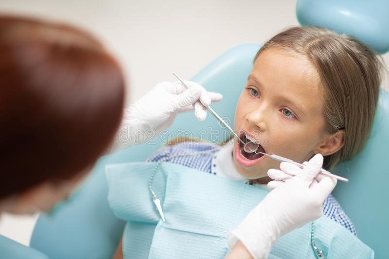 Dark-haired girl opening mouth while visiting dentist royalty free stock photos