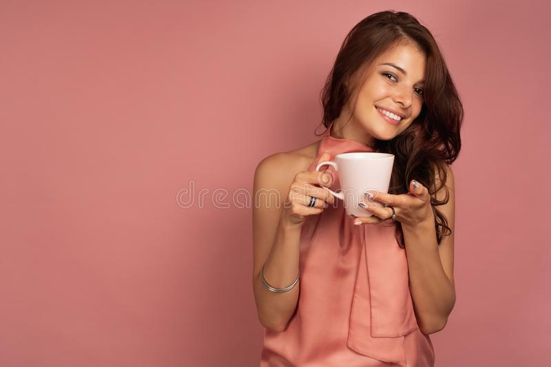 A dark-haired girl in a pink dress stands on a pink background with a white cup in her hands and smiles sweetly with. Her head bowed. Horizontal photo royalty free stock photos