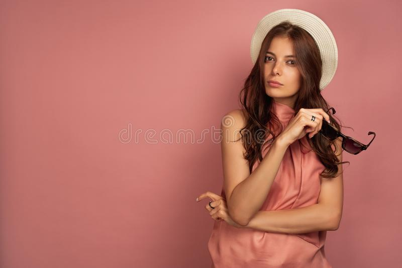 A dark-haired girl in a pink dress and a straw hat holds in glasses and looks into the frame, her head bowed to the side. The dark-haired girl in a pink dress royalty free stock photography
