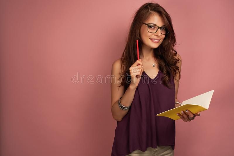 A dark-haired girl in a purple top and glasses stands on a pink background with a notebook and pencil, looks at the. Camera. Horizontal photo stock images