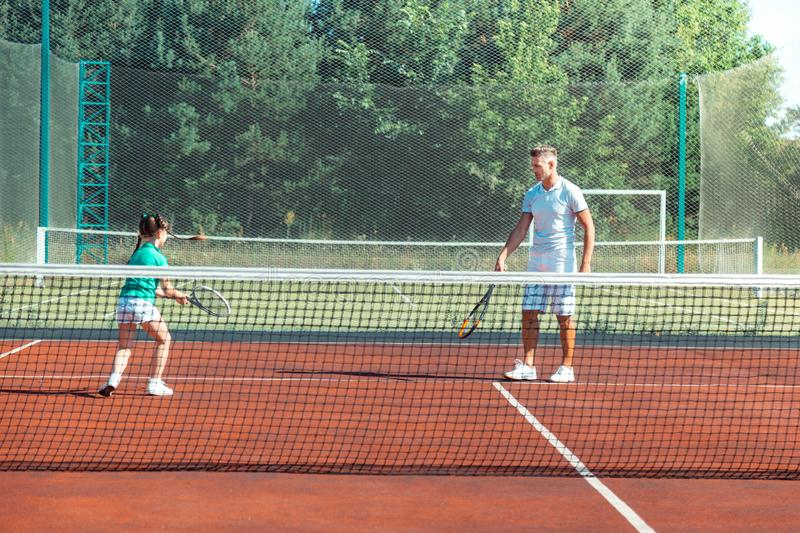 Dark-haired girl running while playing tennis with daddy royalty free stock photo