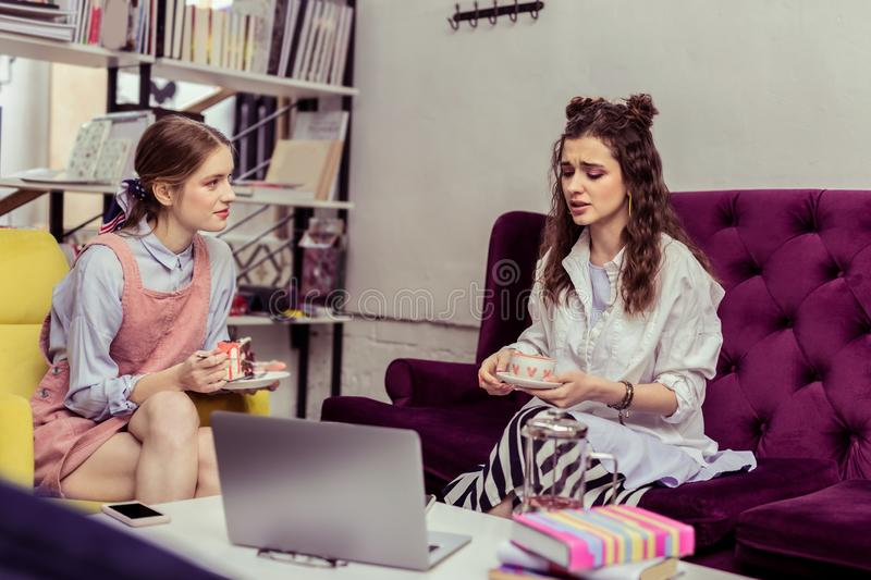 Dark-haired girl with wavy hair complaining about her life to close friend royalty free stock photography