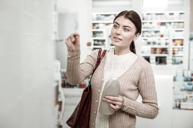 Dark-haired green-eyed woman choosing care cosmetics in pharmacy store royalty free stock photo