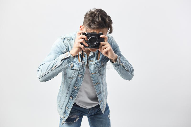 Dark-haired guy dressed in a white t-shirt, jeans and a denim jacket makes photos on camera on the white background in stock image