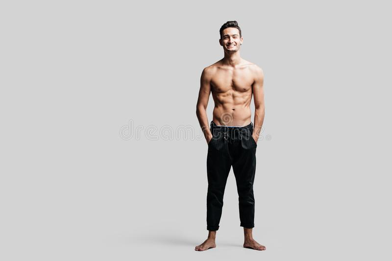 Dark-haired handsome young dancer with bare torso wearing a black sports pants is standing with his hands in his pockets stock photo