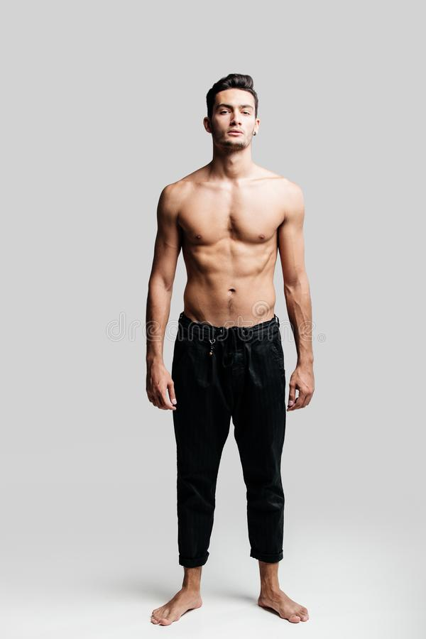 Dark-haired handsome young dancer with bare torso wearing a black sports pants is standing on a white background royalty free stock photo