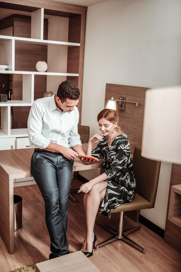 Dark-haired husband holding his tablet showing schedule to wife stock photography