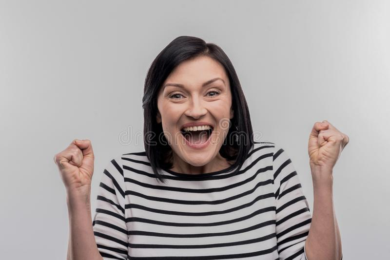 Dark-haired intern feeling happy after reading acceptance letter. Happy intern. Dark-haired intern feeling extremely happy after reading acceptance letter on royalty free stock photography