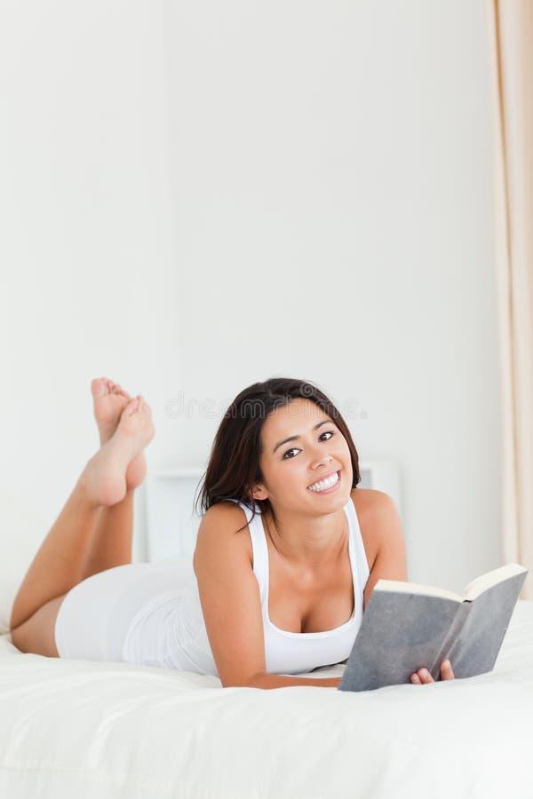 Dark-haired kvinna som ligger på underlag royaltyfri fotografi