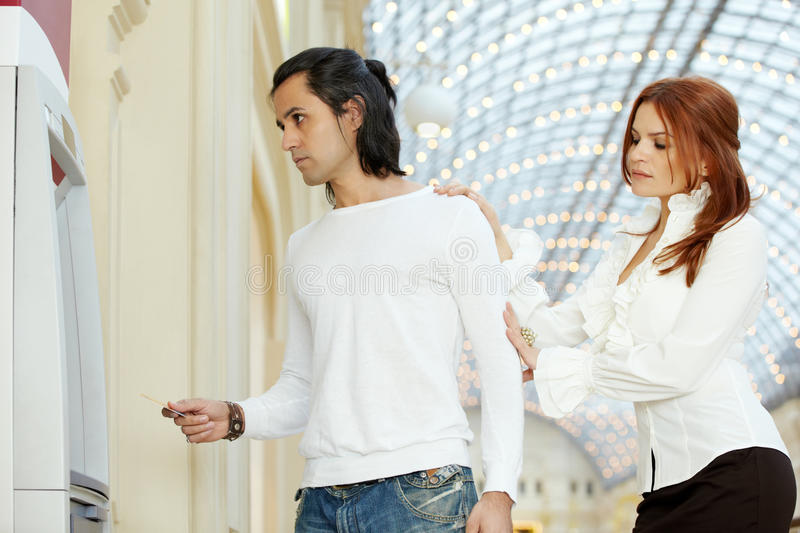 Download Dark-haired Man With Credit Card And Red-haired Woman Stand Stock Image - Image: 28730023