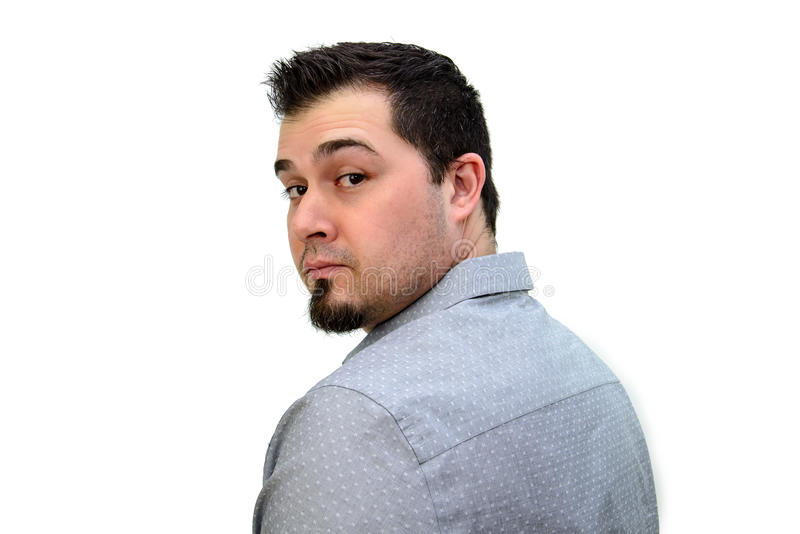 Dark Haired Man in Grey Shirt looking back on white backdrop stock image