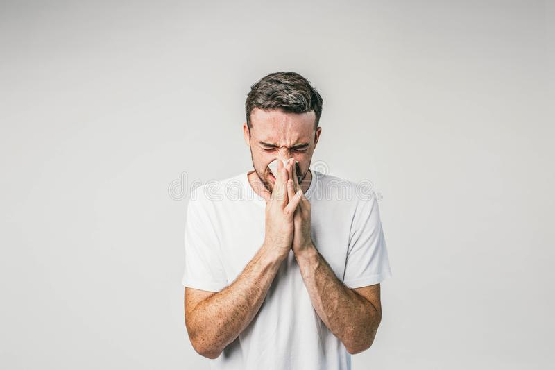 Dark-haired man is standing near the white wall and sneezing. Seems like he caught some cold and soon will be very ill. He need to take some medicine stock photos