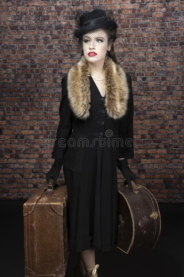 A dark-haired 1940s young woman wearing a black vintage coat dress, hat, and a fur collar. She appears to be at a train station stock images