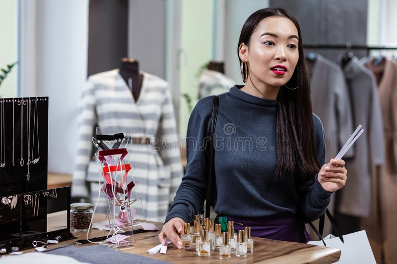 Dark-haired smiling asian lady in a dark-blue blouse testing fragrances royalty free stock photo