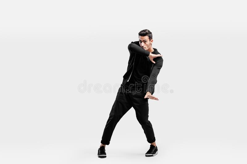 Dark-haired stylish man dressed in a stylish black clothes is dancing street dance. He makes stylized movements with his. Hands royalty free stock photography