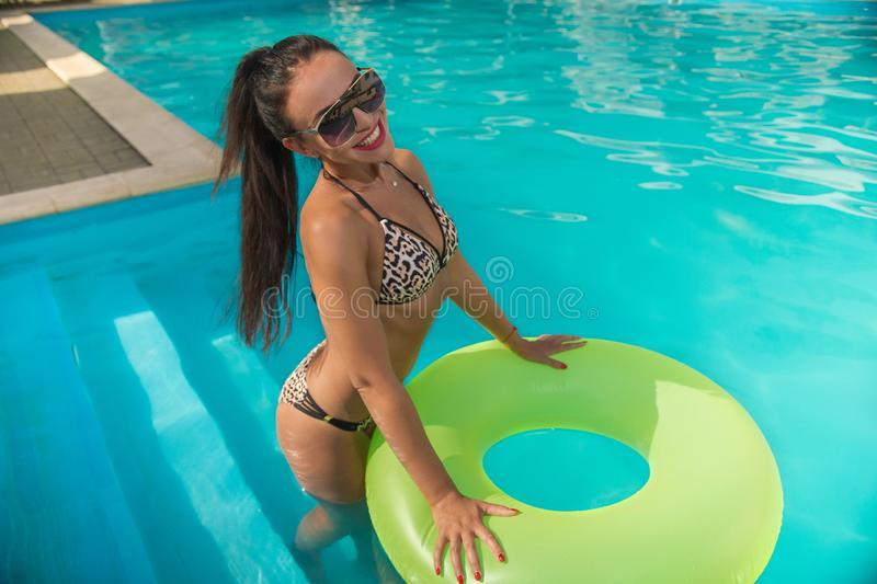 Woman with rubber ring in the pool. A dark-haired tanned girl with a smile on her face in a swimsuit and glasses with a rubber ring stands in the pool stock images