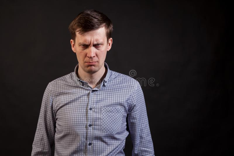 A dark haired white man with distrust expression face. Knit the brows in a plaid shirt and jeans on a black isolated background royalty free stock image