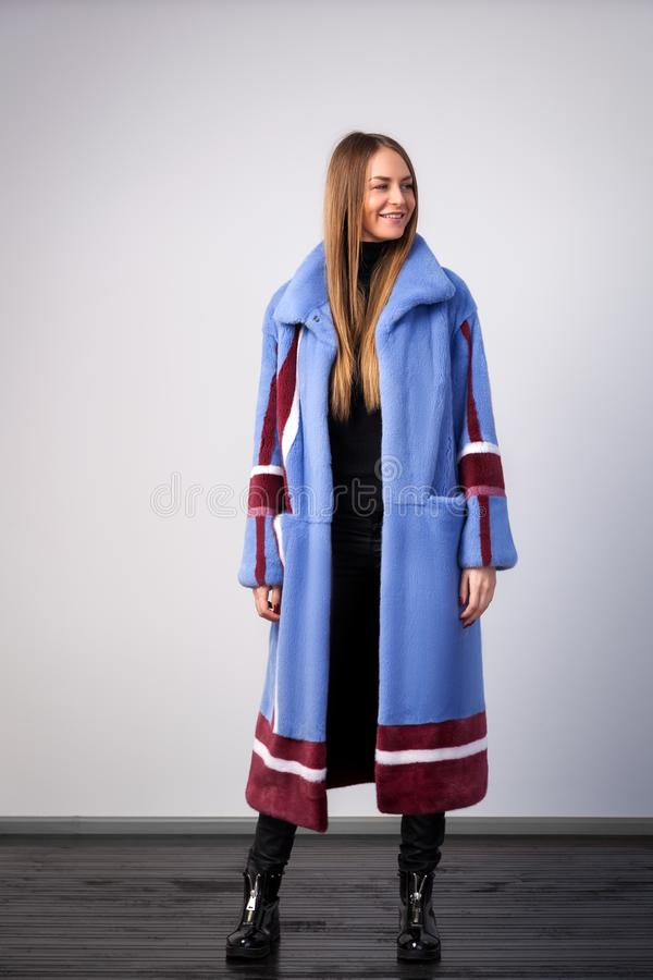 Dark-haired woman in a blue fur coat stock photo