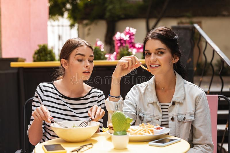 Dark-haired woman feeling jealous while watching her friend eating fries stock photo