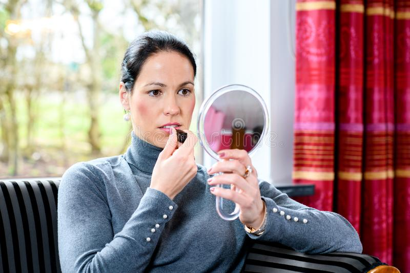 Dark haired woman at home applying make up. Young dark haired woman at home applying make up royalty free stock photography