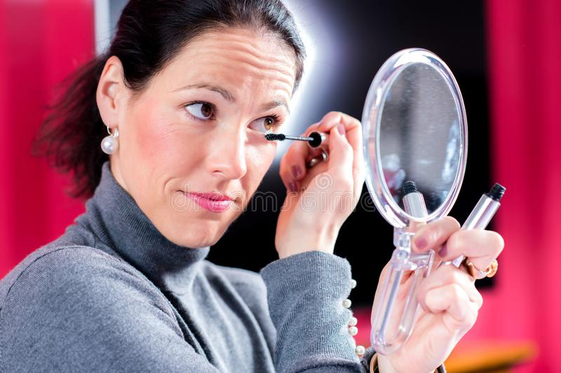 Dark haired woman looking in mirror and applying make up. Young dark haired woman looking in mirror and applying make up royalty free stock images