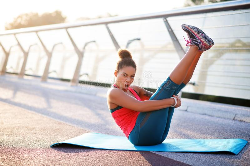 Dark-haired woman making funny face while doing yoga. Making funny face. Dark-haired woman making funny face while doing yoga on sport mat outside royalty free stock image