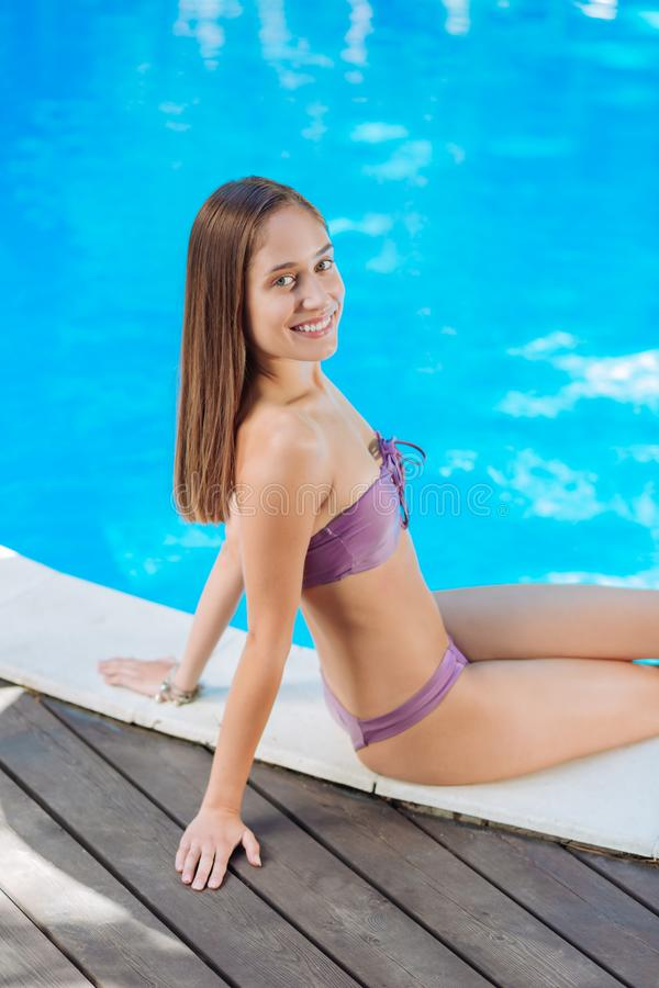 Dark-haired woman in nice swimming suit sitting near outside pool royalty free stock image