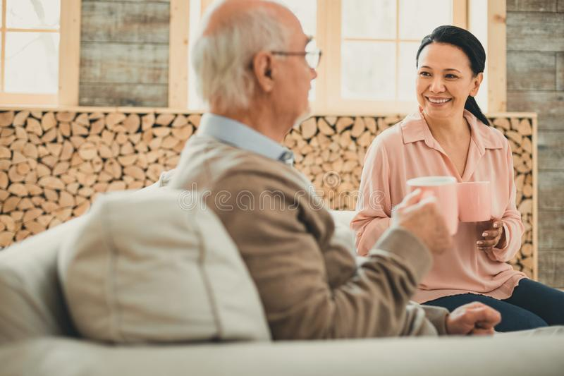 Dark-haired woman and old man sitting on the sofa. Drinking hot tea. Dark-haired women and old men sitting on the sofa with cups of hot drinks royalty free stock photos