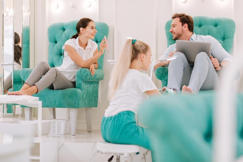 Dark-haired woman showing photo of nail art her man in beauty salon. Photo of nails. Dark-haired women showing photo of nail art her men while having feet stock photos