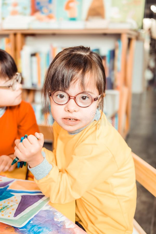 Dark-haired young girl with long bangs and eyeglasses wearing yellow sweater. Cute children. Dark-haired young girl with long bangs and eyeglasses wearing yellow stock photography
