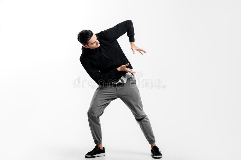 Dark-haired young man wearing a black sweatshirt and gray pants is dancing street dance. He makes stylized movements royalty free stock image