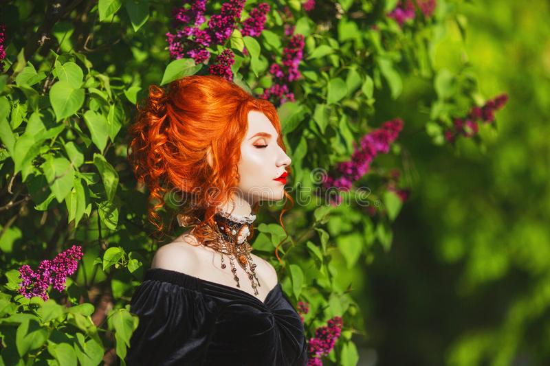 Dark halloween attire. Goth woman with pale skin and red hair in black victorian gown and renaissance necklace on neck. royalty free stock photos