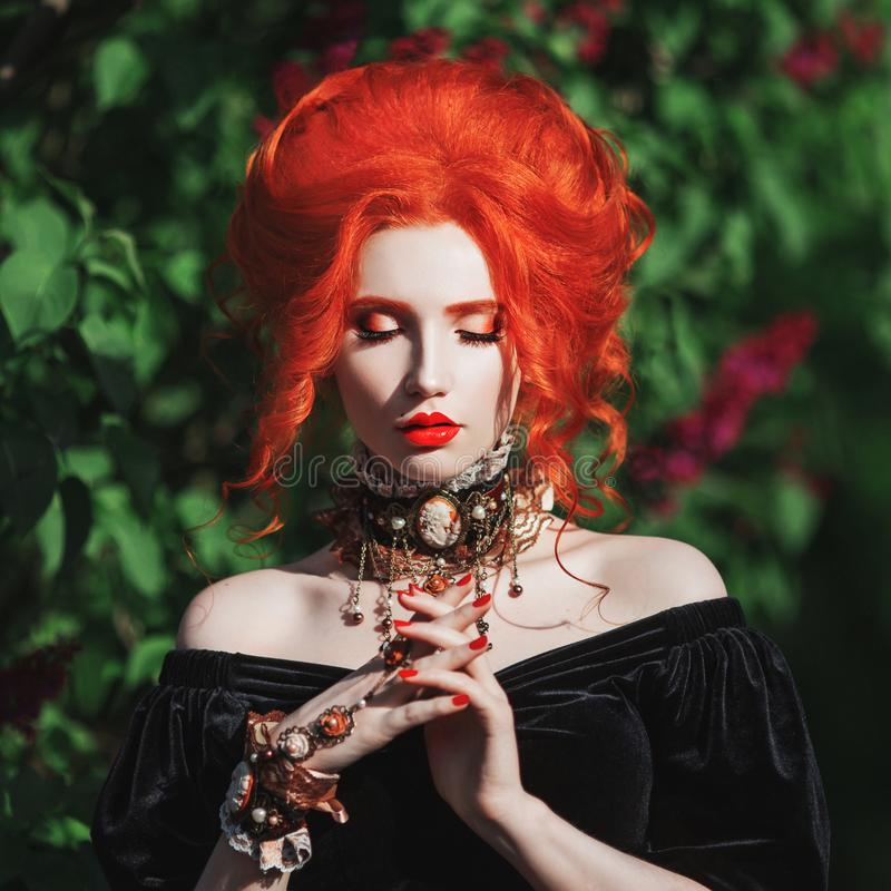 Dark halloween attire. Gothic woman witch with pale skin and red hair in black gown and baroque necklace on neck. stock photos