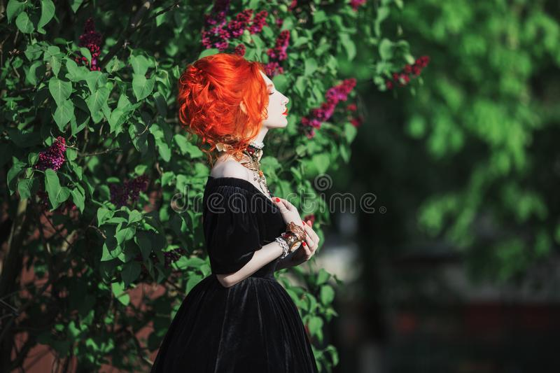 Dark halloween attire. Gothic woman witch with pale skin and red hair in black gown and renaissance necklace on neck. stock photos