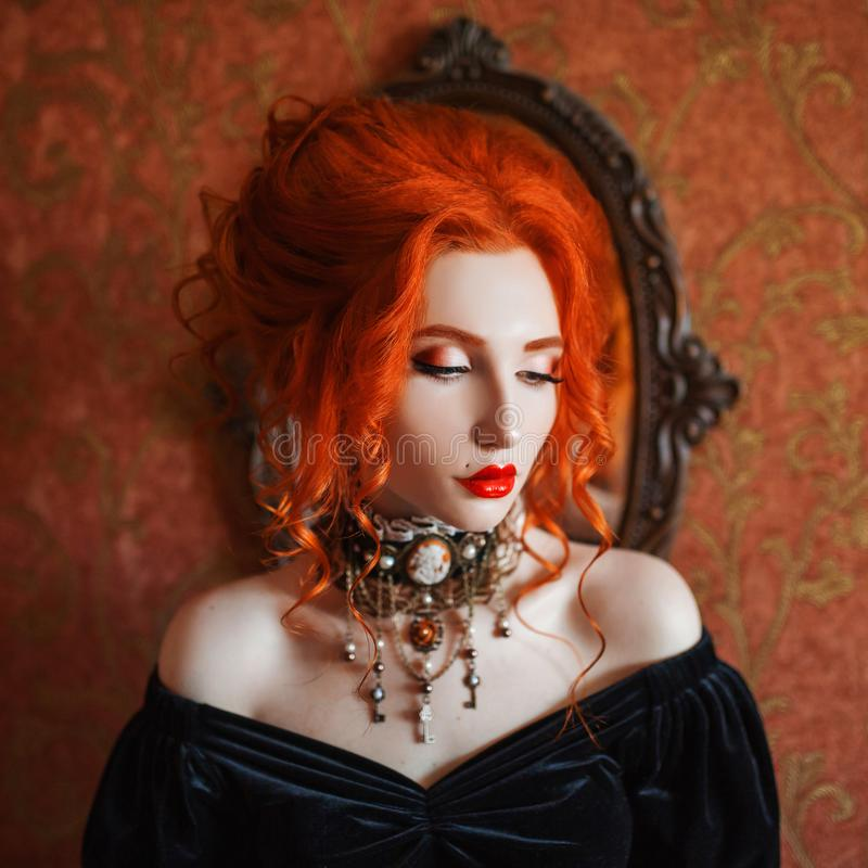 Dark halloween attire. Redhead gothic woman is vampire with pale skin in a black edwardian dress and a necklace on neck. Edwardian redhead girl witch with red stock photos