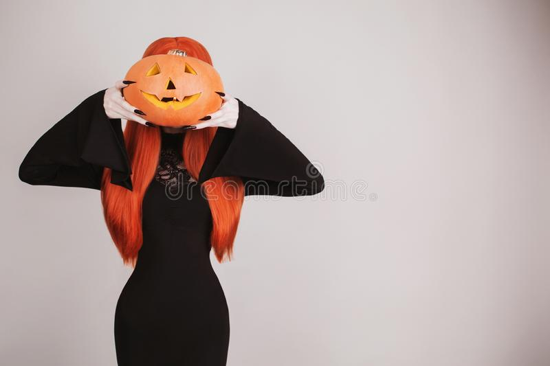 Dark halloween costume and copyspace. Spooky witch with red lips. Scary gothic woman vampire in black dress holding pumpkin jack. royalty free stock images