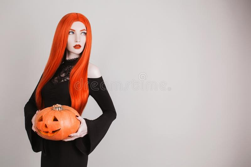 Dark halloween costume. Gothic woman vampire with pale skin and red hair in black dress holding pumpkin. Girl witch with red lips. stock photography