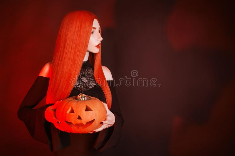Dark halloween costume. Scary witch with red lips in hell. Gothic woman vampire with pale skin and red hair in black dress holding stock image