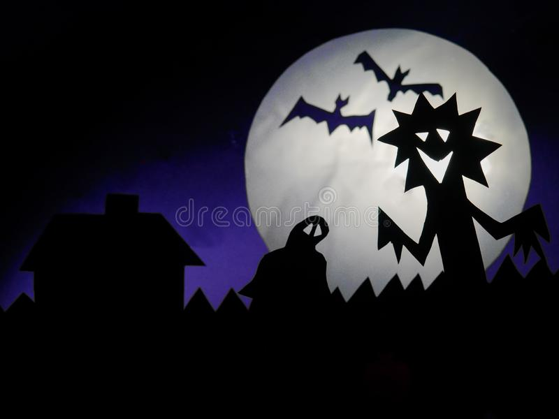Dark Halloween season background with moon in the background and scary creatures silhouettes. Alien, bats, and funny monster royalty free stock photos