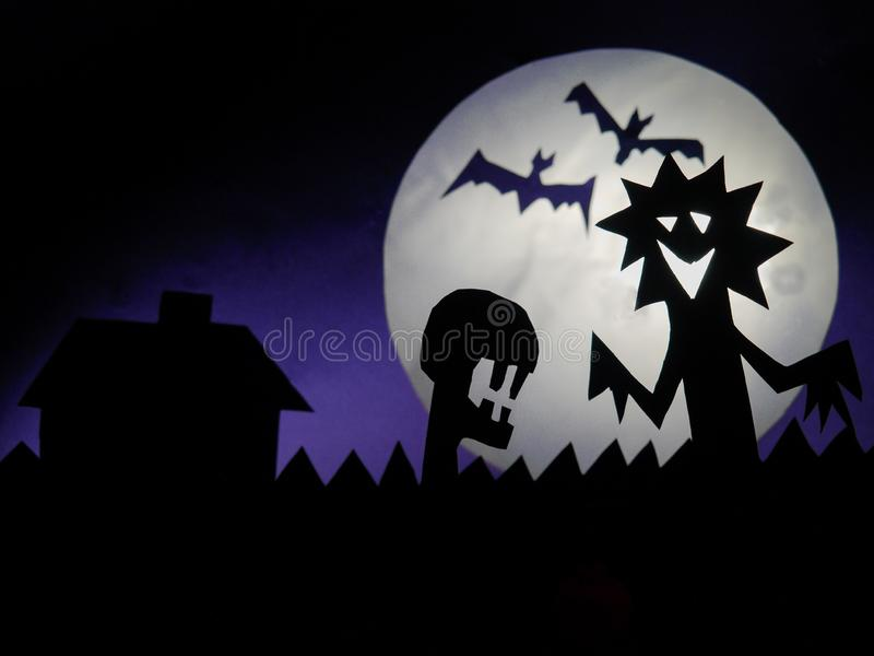 Dark Halloween season background with moon in the background and scary creatures silhouettes. Alien scull, bats, and funny monster stock photos