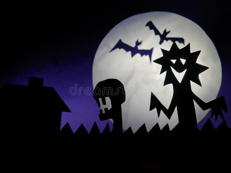 Dark Halloween season background with moon in the background and scary creatures silhouettes. Alien scull, bats, and funny monster stock photo