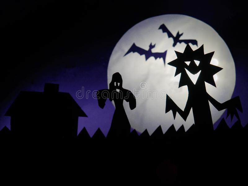 Dark Halloween season background with moon in the background and scary creatures silhouettes. Ghost, bats, and funny monster. Scary monsters silhouettes on fool stock photos