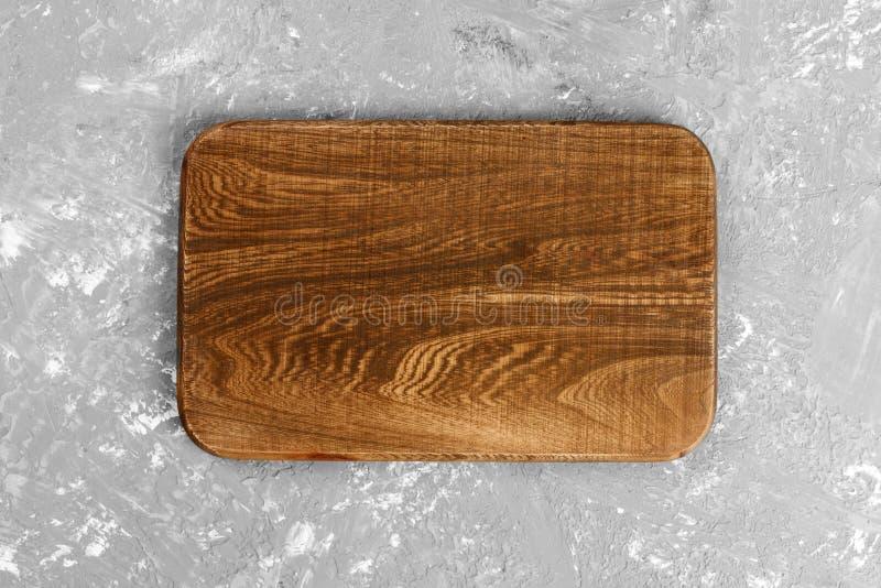 Dark handmade wooden cutting board on dark background. Top view stock image