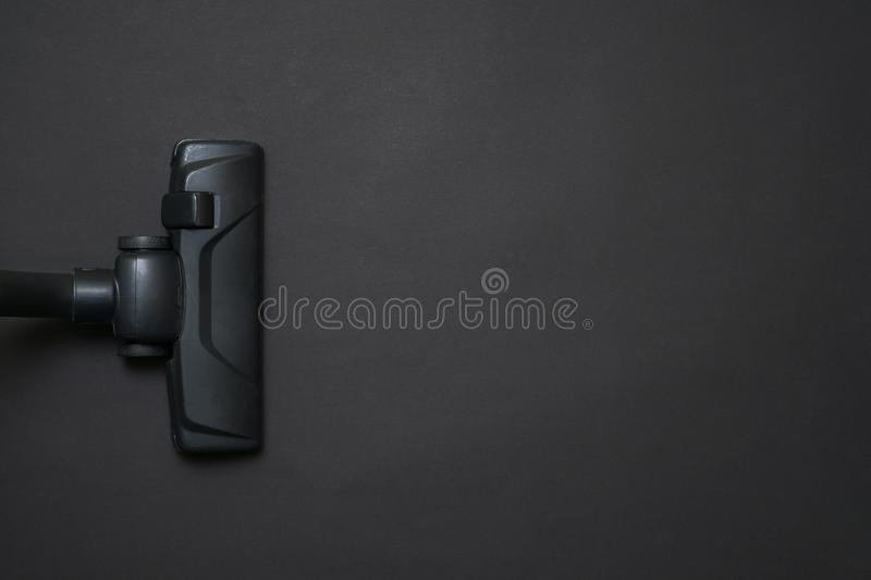 Dark head of a modern vacuum cleaner being used while vacuuming stock image