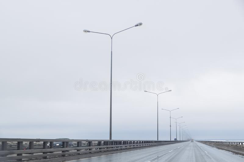 Dark highway in cloudy weather after rain.straight way with dramatic clouds. empty highway, cloudy sky, lighting on the. Dark highway in cloudy weather.empty stock images