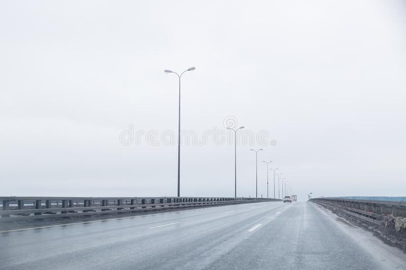 Dark highway in cloudy weather after rain.straight way with dramatic clouds. empty highway, cloudy sky, lighting on the royalty free stock photo