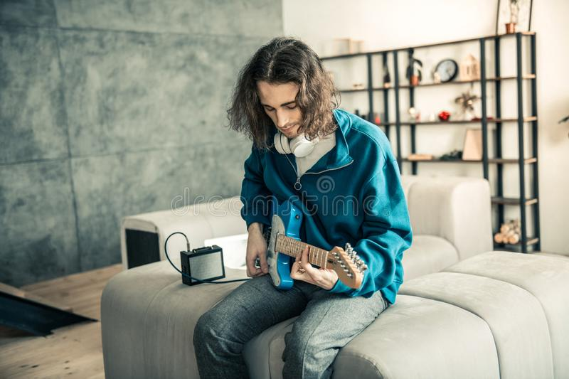 Dark-hired good-looking guy with wavy haircut being concentrated. Performing music. Dark-hired good-looking guy with wavy haircut being concentrated on personal stock photography